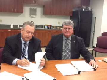 Richard Genovesse, Ciber's executive vice president and chief operating officer signs the ctcLink project contract while MIke Scroggins, SBCTC's deputy executive director of information technology and chief information officer looks pleased to be in the final stages of the process.